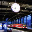 Railway station with the red train and clock - Stock Photo