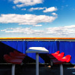 Red chairs on a blue background on the ferry in the spring - Stock Photo