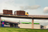 Truck with logs traveling at speed on a viaduct bridge — Stock Photo