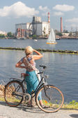 Girl with bicycle looking at the sailing ship on the river — Foto Stock