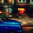 Stock Photo: Taxis in London at speed over houses