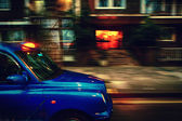 Taxis in London at a speed over the houses — Stock Photo