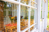 Reflection of autumn park in glasses summer terrace — Stock Photo
