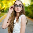Royalty-Free Stock Photo: Attractive blonde woman wearing eyeglasses and white blouse at summer green park