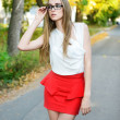 Attractive blonde woman wearing eyeglasses and white blouse at summer green park — Stock fotografie