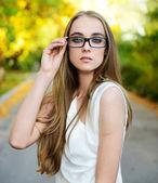 Aantrekkelijke blonde vrouw dragen brillen en witte blouse in zomer groen park — Stockfoto