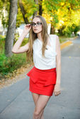Attractive blonde woman wearing eyeglasses and white blouse at summer green park — Stock Photo