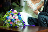 Wedding bouquet near bride and groom — Stock Photo