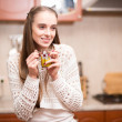 Happy young woman holding cup of tea at the kitchen — Stock Photo #18414921