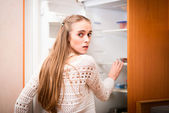 Young woman looking for food in refrigerator — Stock Photo