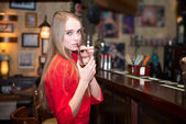 Young beautiful woman drinking cocktails at the bar — Stock Photo