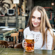beautiful woman drinking beer at the cafe — Stock Photo