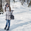 Beautiful happy woman walking in the winter forest — Stock Photo #19672357