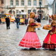 Two woman in traditional clothes standing in the square in old city Lvov - Stock Photo