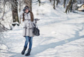 Beautiful happy woman walking in the winter forest — Stock Photo