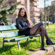 Beautiful woman sitting on the bench in the city park — Foto de Stock