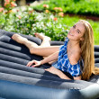Happy young woman lying on the mattress in the garden — Stock Photo