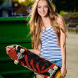 Happy sporty woman with skateboard standing outdoors — Stock Photo
