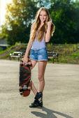 Bella donna felice tiene il suo skateboard all'aperto — Foto Stock