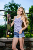 Glücklich sportliche frau mit skateboard stehen im freien — Stockfoto