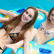 Two happy women in bikini standing near water slide in the aqua park and — Stock Photo