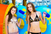 Two smiling women in bikini standing near water slide in the aqua park and holding rubber ring — Stock Photo