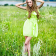 Beautiful woman in green dress posing on the field — Stock Photo