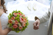 Bride ang groom holding wedding bouquet — Stock Photo