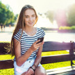 Young beautiful woman honding mobile phone in hand and sitting on the bech in the park — Stock Photo
