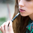 Woman smoking electronic cigarette outdoors — Stock Photo