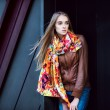 Beautiful fashion woman wearing leather coat and scarf posing against modern wall — Stok fotoğraf