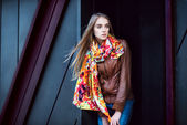 Beautiful fashion woman wearing leather coat and scarf posing against modern wall — Stock Photo