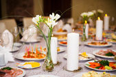 Table served with a meal in a restaurant with candles and flowers — Stock Photo