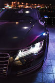 Luxury car at the parking in front of the night city lights — Stock Photo