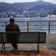 Lonely man sitting on the bench near the lake — Stock Photo