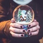 Woman holding snow globe on the Christmas fair — Stock Photo