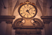 Dark grunge vintage clock on antique building — Stock Photo