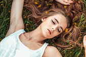 Beautiful girl is relaxing lying on the grass — Stock Photo