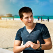 Young man using smartphone sitting on the city beach — Stok fotoğraf