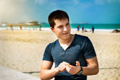 Young man using smartphone sitting on the city beach — Stock Photo