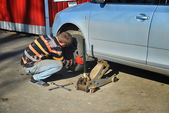 Man changing tires on the car at the service station — Stock Photo