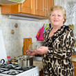 Senior woman cooking at the kitchen — Stock Photo