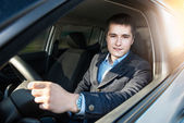 Young businessman driving a car — Stock Photo