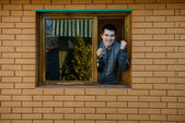 Happy man showing keys from the window of his new house — Stock Photo