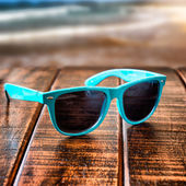 Sunglasses on wooden desk at the summer beach — Stock Photo