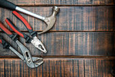 Hammer and pliers on wooden background — Stock Photo