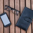 Mobile phone, glasses, calculator, notepad on wooden table. Business accessories concept. — Stock Photo #46884643