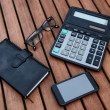 Mobile phone, glasses, calculator, notepad on wooden table. Business accessories concept. — Stock Photo