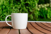 Coffee cup in green garden on table — Stock Photo