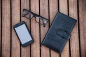 Mobile phone, glasses, calculator, notepad on wooden table. Business accessories concept. — Foto de Stock